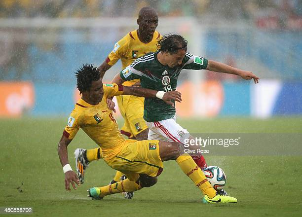 Cedric Djeugoue of Cameroon challenges Andres Guardado of Mexico in the first half during the 2014 FIFA World Cup Brazil Group A match between Mexico...