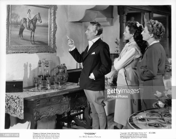 Cedric Hardwicke showing painting to Laraine Day and Judith Anderson and stare at each other in a scene from the film 'Tycoon' 1947