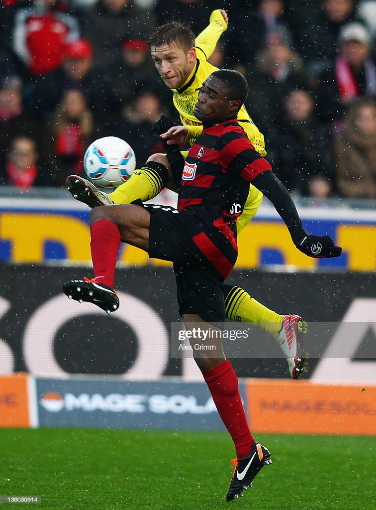 Cedric Makiadi (front) of Freiburg is challenged by <a gi-track='captionPersonalityLinkClicked' href=/galleries/search?phrase=Jakub+Blaszczykowski&family=editorial&specificpeople=2290714 ng-click='$event.stopPropagation()'>Jakub Blaszczykowski</a> of Dortmund during the Bundesliga match between SC Freiburg and Borussia Dortmund at Badenova Stadium on December 17, 2011 in Freiburg im Breisgau, Germany.