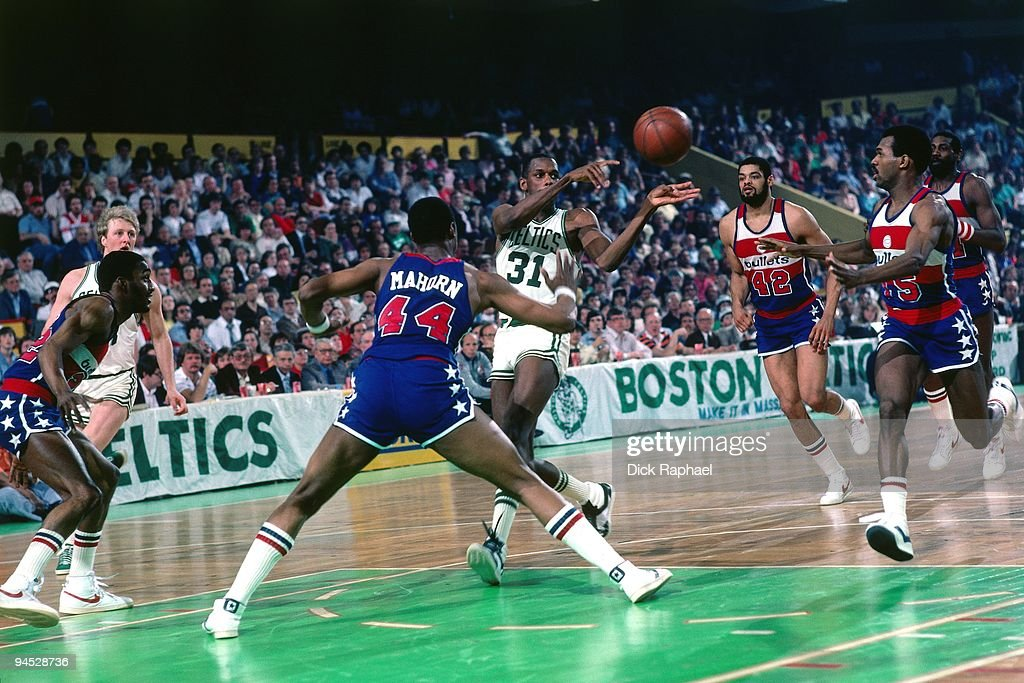 Cedric Maxwell of the Boston Celtics passes against Rick Mahorn of the Washington Bullets during a game played in 1982 at the Boston Garden in Boston...