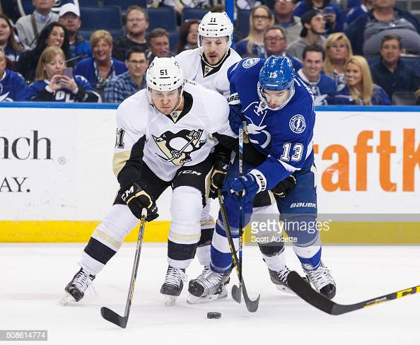 Cedric Paquette of the Tampa Bay Lightning battles for the puck against Derrick Pouliot and Kevin Porter of the Pittsburgh Penguins during the first...