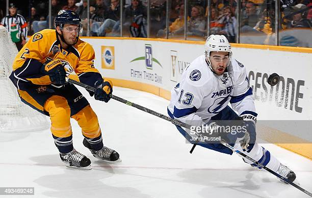 Cedric Paquette of the Tampa Bay Lightning eyes the puck against Anthony Bitetto of the Nashville Predators during an NHL game at Bridgestone Arena...