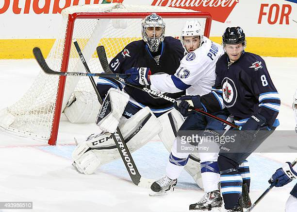Cedric Paquette of the Tampa Bay Lightning gets in between goaltender Ondrej Pavelec and Jacob Trouba of the Winnipeg Jets as they keep an eye on the...