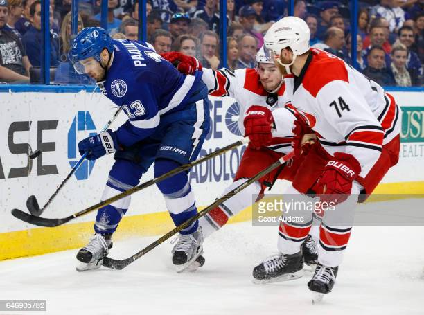 Cedric Paquette of the Tampa Bay Lightning skates against Brett Pesce and Jaccob Slavin of the Carolina Hurricanes during the third period at Amalie...