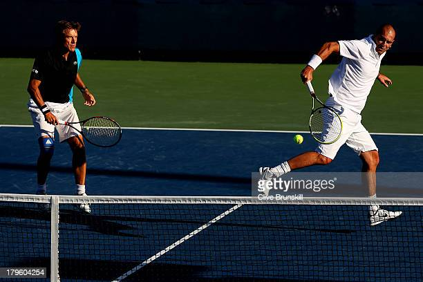 Cedric Pioline of France plays a backhand next to his partner Mats Wilander of Sweden during their men's champions doubles match against John McEnroe...