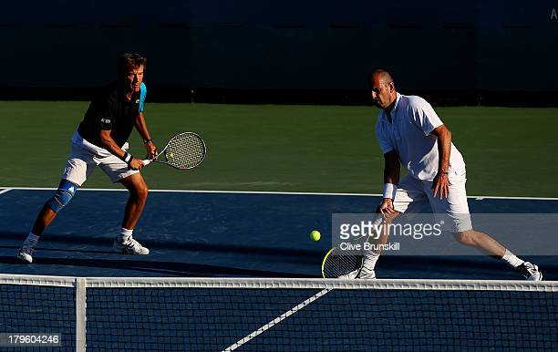 Cedric Pioline of France plays a forehand next to his partner Mats Wilander of Sweden during their men's champions doubles match against John McEnroe...