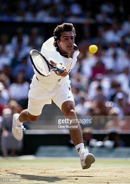 Cedric Pioline of France stretches to make a forehand return against Pete Samprass during their Men's Singles final match at the Wimbledon Lawn...