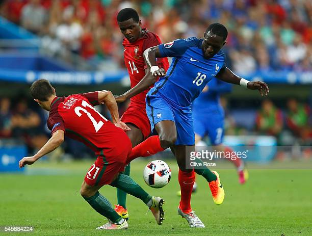 Cedric Soares and William Carvalho of Portugal combine to tackle Moussa Sissoko of France during the UEFA EURO 2016 Final match between Portugal and...