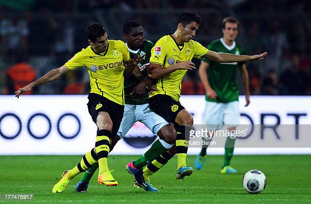 Cedrick Makiadi of Bremen is challenged by Henrikh Mkhitaryan and Nuri Sahin of Dortmund during the Bundesliga match between Borussia Dortmund and...