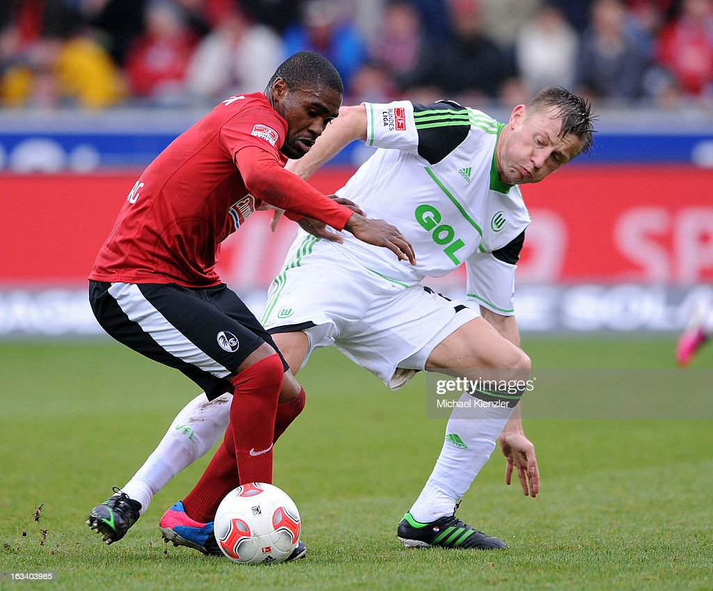 Cedrick Makiadi (L) of Freiburg challenges Ivica Olic during the Bundesliga match between SC Freiburg and VfL Wolfsburg at MAGE SOLAR Stadium on March 9, 2013 in Freiburg, Germany.
