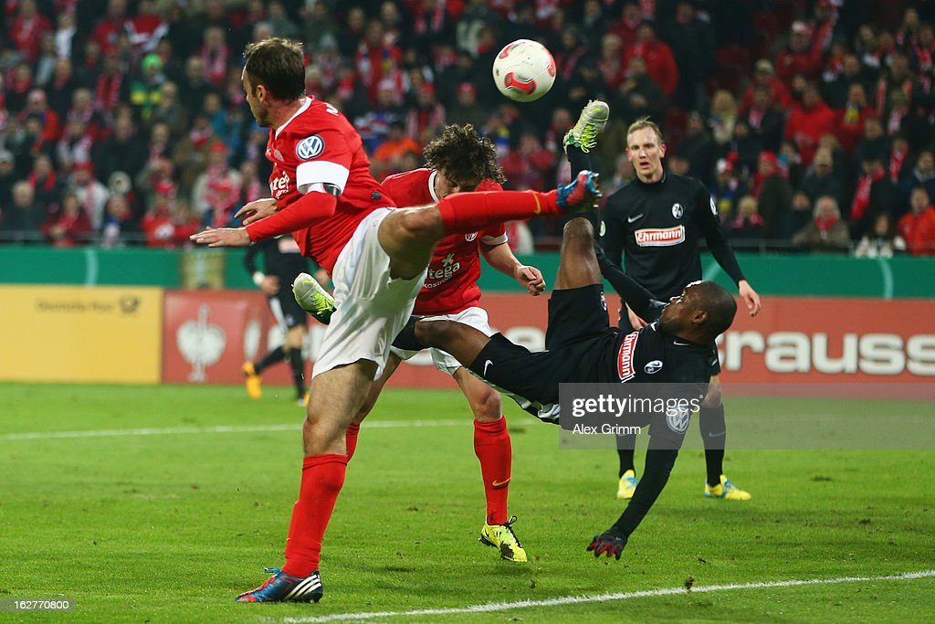 <a gi-track='captionPersonalityLinkClicked' href=/galleries/search?phrase=Cedrick+Makiadi&family=editorial&specificpeople=635003 ng-click='$event.stopPropagation()'>Cedrick Makiadi</a> of Freiburg tries to score with a bicycle-kick against Julian Baumgartlinger (back) and <a gi-track='captionPersonalityLinkClicked' href=/galleries/search?phrase=Nikolce+Noveski&family=editorial&specificpeople=649271 ng-click='$event.stopPropagation()'>Nikolce Noveski</a> of Mainz during the DFB Cup Quarter Final match between FSV Mainz 05 and SC Freiburg at Coface Arena on February 26, 2013 in Mainz, Germany.
