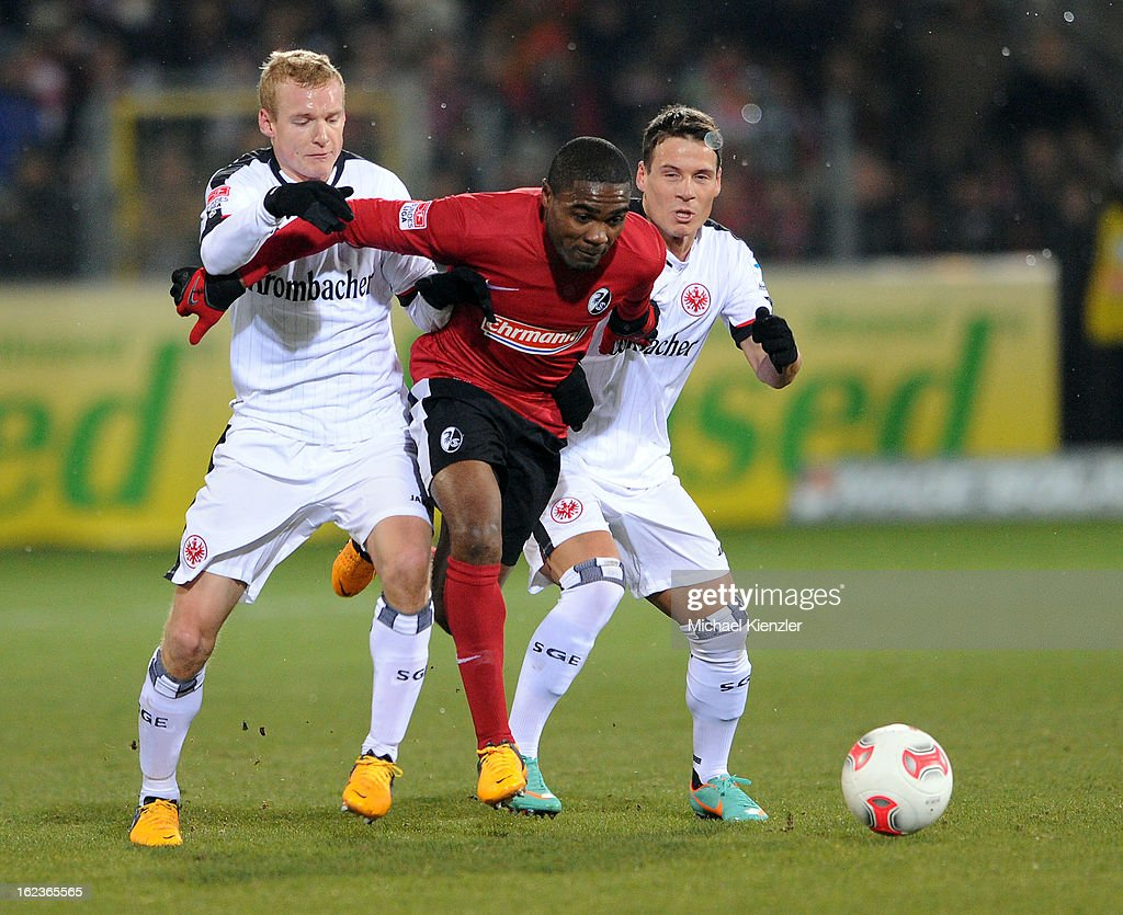 Cedrick Makiadi (middle) of Freiburg was challenged by Sebastian Rode (l) and Stefano Celozzi (r) during the Bundesliga match between SC Freiburg and Eintracht Frankfurt at MAGE SOLAR Stadium on February 22, 2013 in Freiburg, Germany.