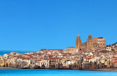 Houses along the shoreline and cathedral in background, Cefalù, Sicily