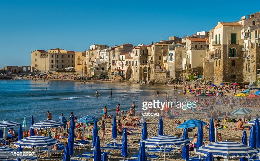 Cefalù waterfront with peole relaxing on a sunny summer day. Sicily, southern Italy. : Foto stock