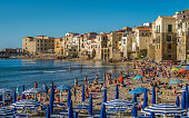 Cefalù waterfront with peole relaxing on a sunny summer day. Sicily, southern Italy.