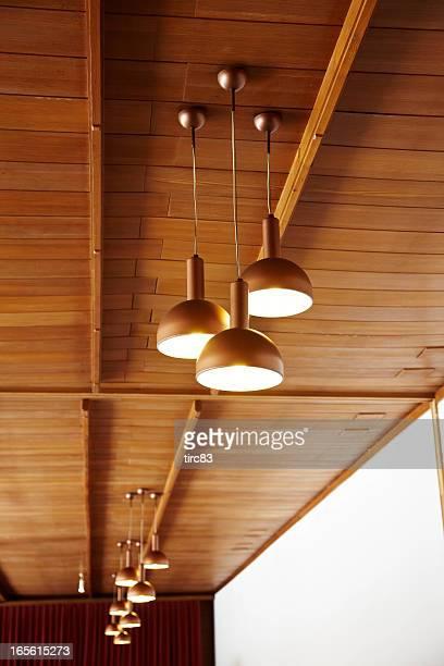 Der Decke hängenden Lampen mit Holzvertäfelung
