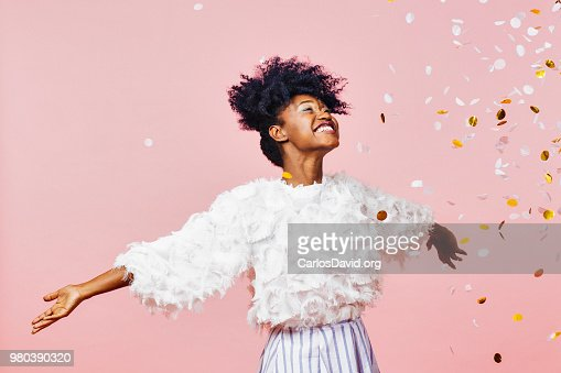 Celebrate happiness and joy- young girl throwing confetti : Stock Photo