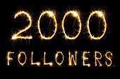 2000 Followers text on black background made with sparklers