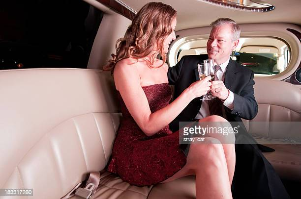 Celebrating couple in limo with champagne glasses