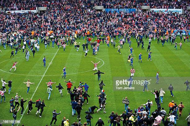 Celebrating fans invade the pitch as Stoke City gain promotion to the Premier League after a 00 draw with Leicester City in their Championship match...