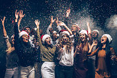 Group of beautiful young people in Santa hats throwing colorful confetti and looking happy