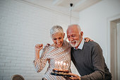 Mature couple celebrating holding a birthday cake