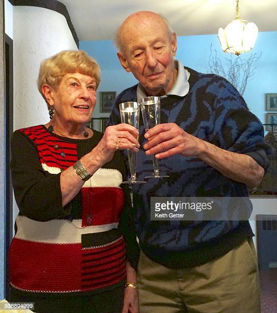 Celebrating their 65th Wedding Anniversary a man and woman toast the occasion with sparkling white wine in flute glasses