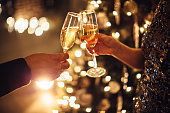 Couple holding glasses of champagne in front of Christmas tree. Toasting to each other. Evening or night.