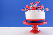 UK celebration cake with flags, marshmallow and candy decorations on a red cake stand on a white table against a blue background.