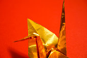 Celebration material of Japan. Golden folded-paper crane. red background