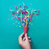 Celebration,party backgrounds concepts ideas with hand holding colorful confetti,streamers.Flat lay design