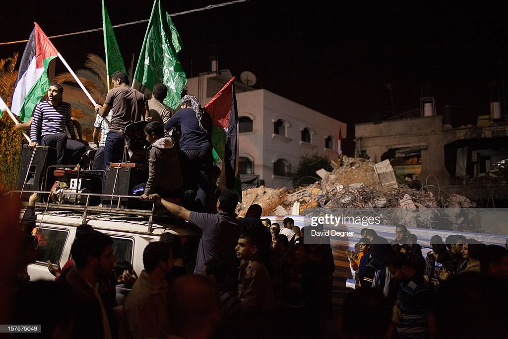 Celebrators stopped in front of the crumbled house of the Eldalo, where 11 people were killed by an Israeli attack in Gaza City, Gaza on November 21, 2012. After the announcement of a ceasefire crowds gathered in the streets of Gaza to celebrate, finally converging on Shifa hospital.