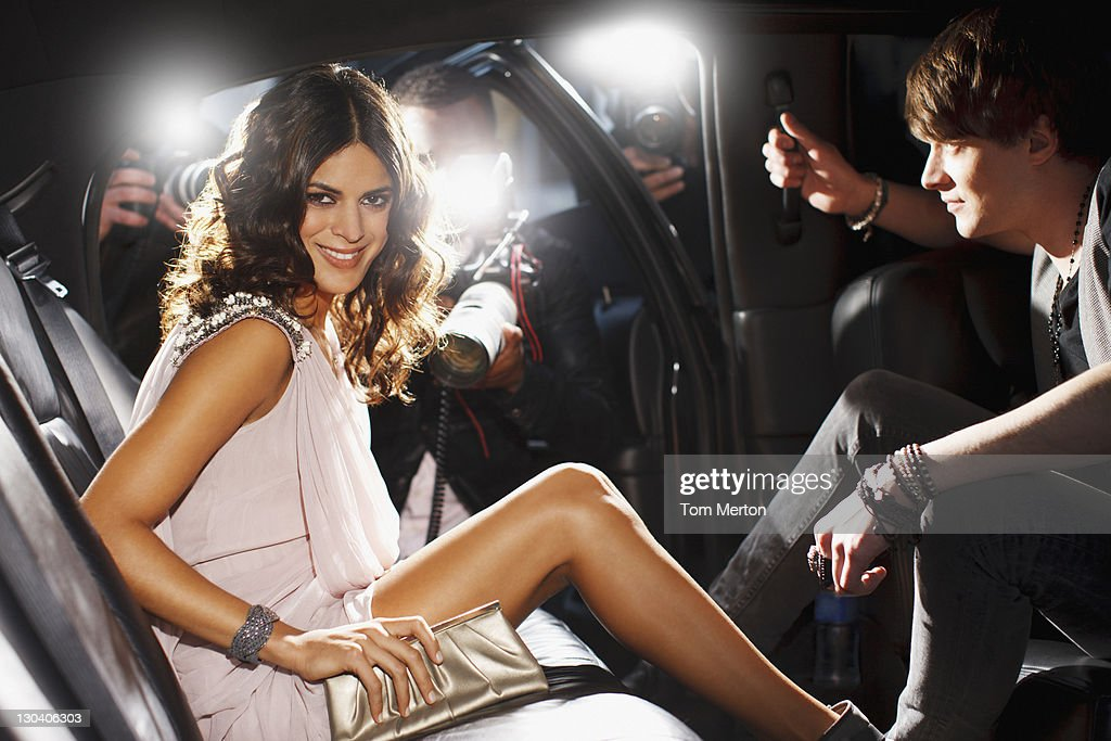 Celebrities emerging from car towards paparazzi : Stock Photo