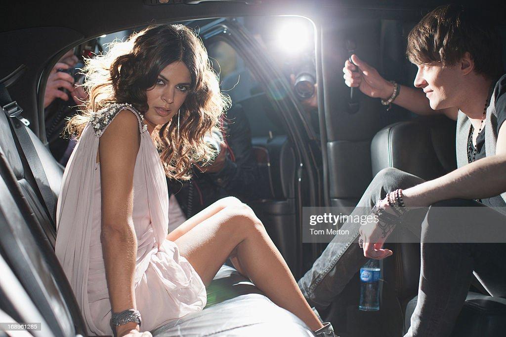 Celebrities emerging from car towards paparazzi