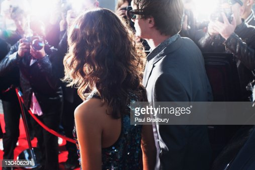 Celebrities posing for paparazzi on red carpet