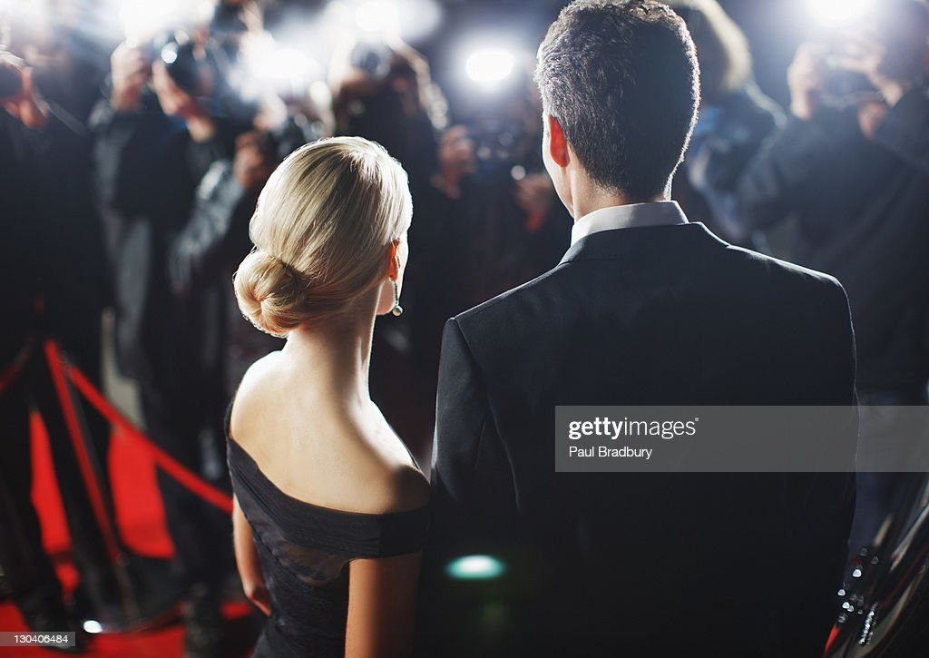 Celebrities posing for paparazzi on red carpet : Stock Photo