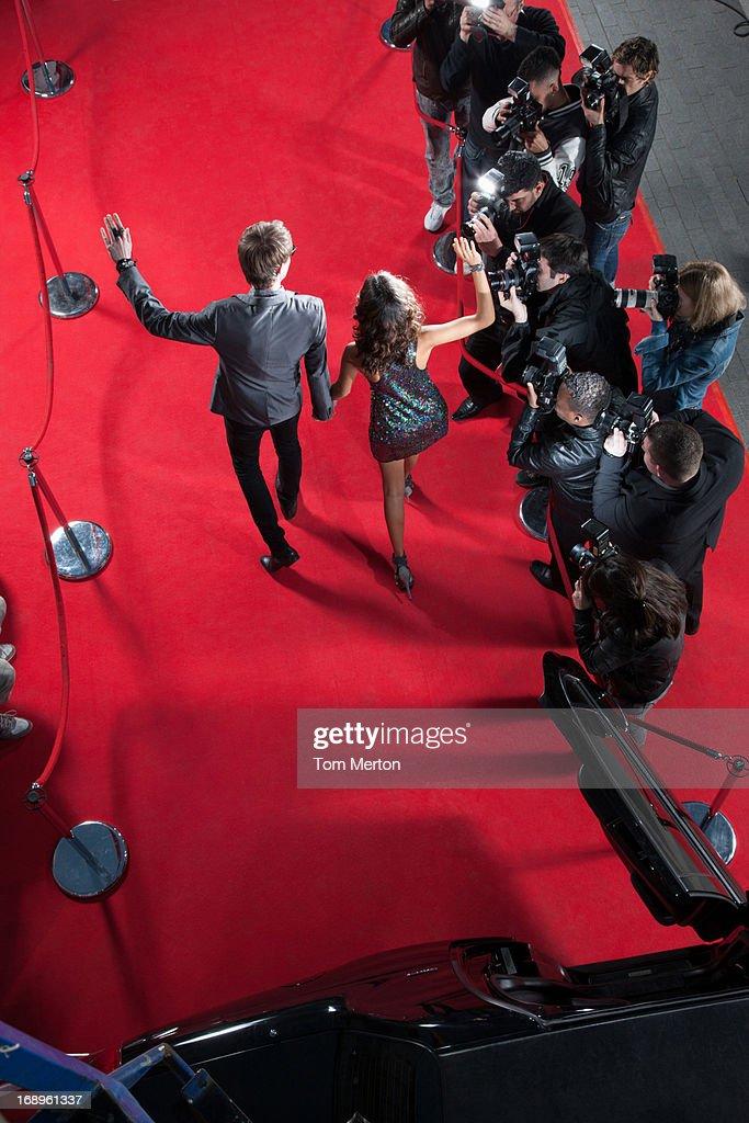Celebrities waving to paparazzi on red carpet : Stock Photo