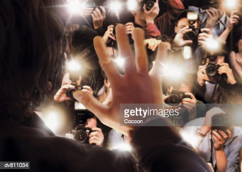 Celebrity Being Photographed By a Large Group of Paparazzi