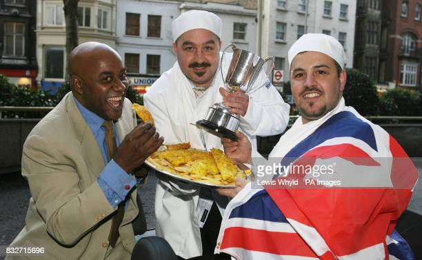 Celebrity chef Ainsley Harriott presents brothers Mark and Pete Petrou with the National Fish Chip Shop of the Year Award at a ceremony in London