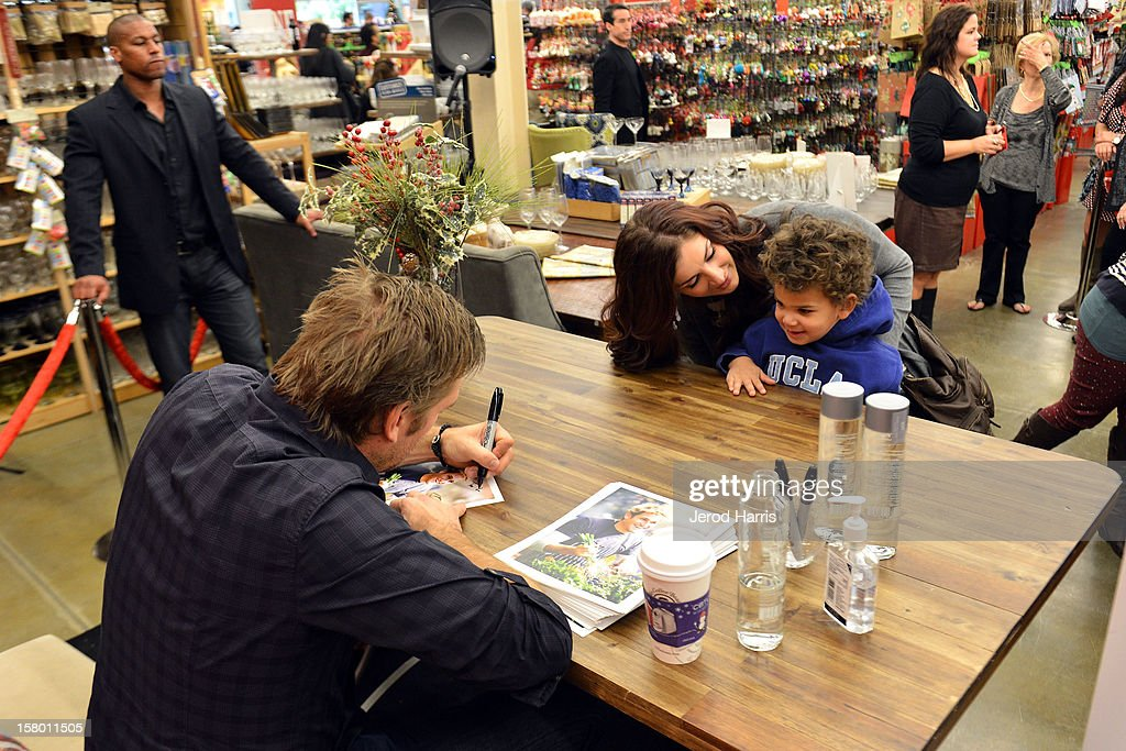 Celebrity Chef Curtis Stone (L) signs an autograph for 2 year old Eli Simmons and his mom Natalia at Cost Plus World Market's Share the Joy event at Cost Plus World Market on December 8, 2012 in Los Angeles, United States.
