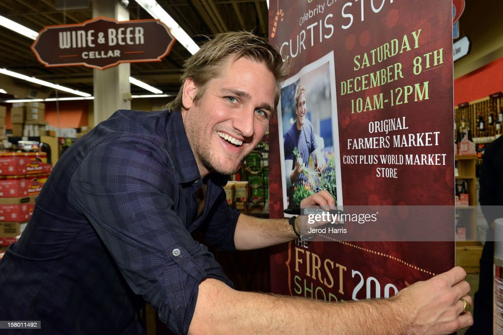Celebrity Chef <a gi-track='captionPersonalityLinkClicked' href=/galleries/search?phrase=Curtis+Stone&family=editorial&specificpeople=215291 ng-click='$event.stopPropagation()'>Curtis Stone</a> signs an event banner at Cost Plus World Market's Share the Joy at Cost Plus World Market on December 8, 2012 in Los Angeles, United States.