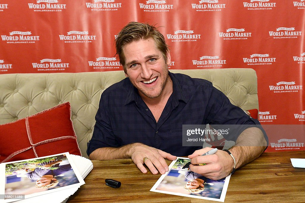Celebrity Chef <a gi-track='captionPersonalityLinkClicked' href=/galleries/search?phrase=Curtis+Stone&family=editorial&specificpeople=215291 ng-click='$event.stopPropagation()'>Curtis Stone</a> signs autographs for fan at Cost Plus World Market's Share the Joy event at Cost Plus World Market on December 8, 2012 in Los Angeles, United States.