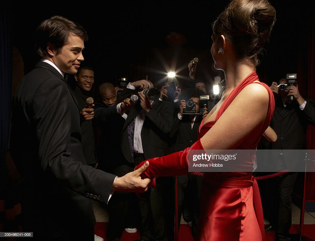 Celebrity couple in evening wear being photographed by paparazzi : Stock Photo