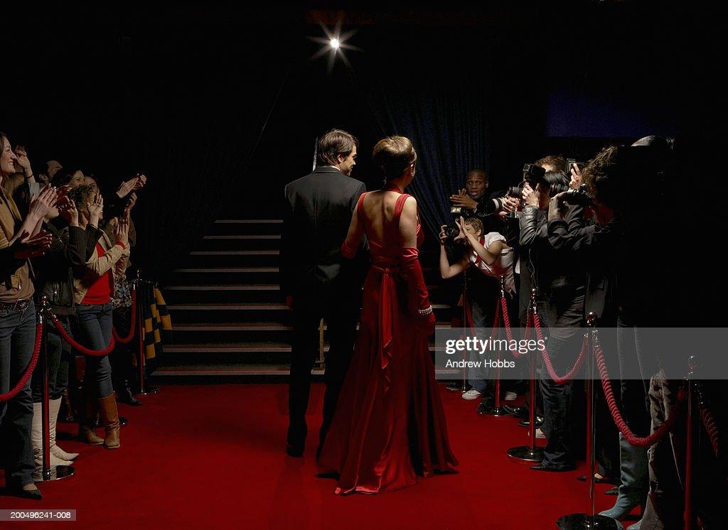 Celebrity couple in evening wear walking on red carpet, rear view