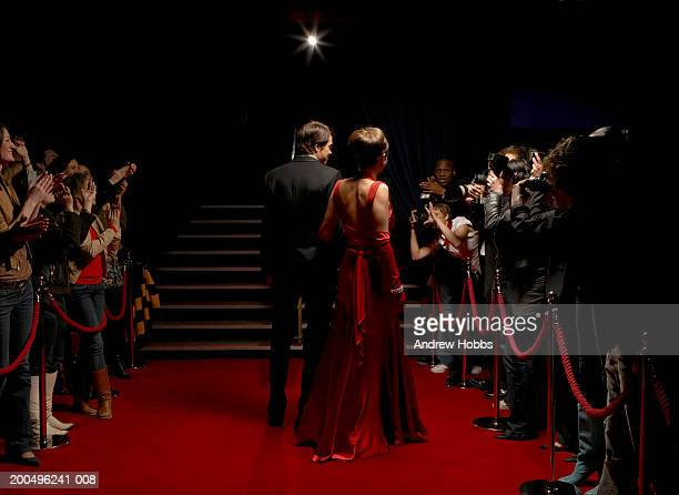 Celebrity couple in evening wear walking on red carpet, rear view