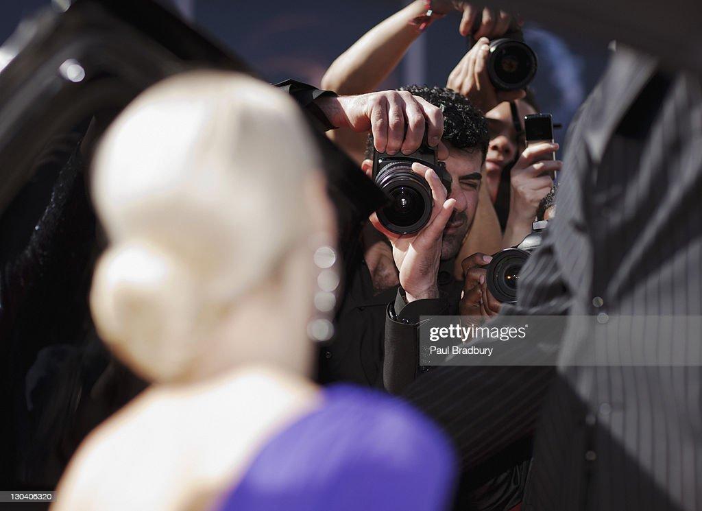 Celebrity emerging from car towards paparazzi : Stock Photo