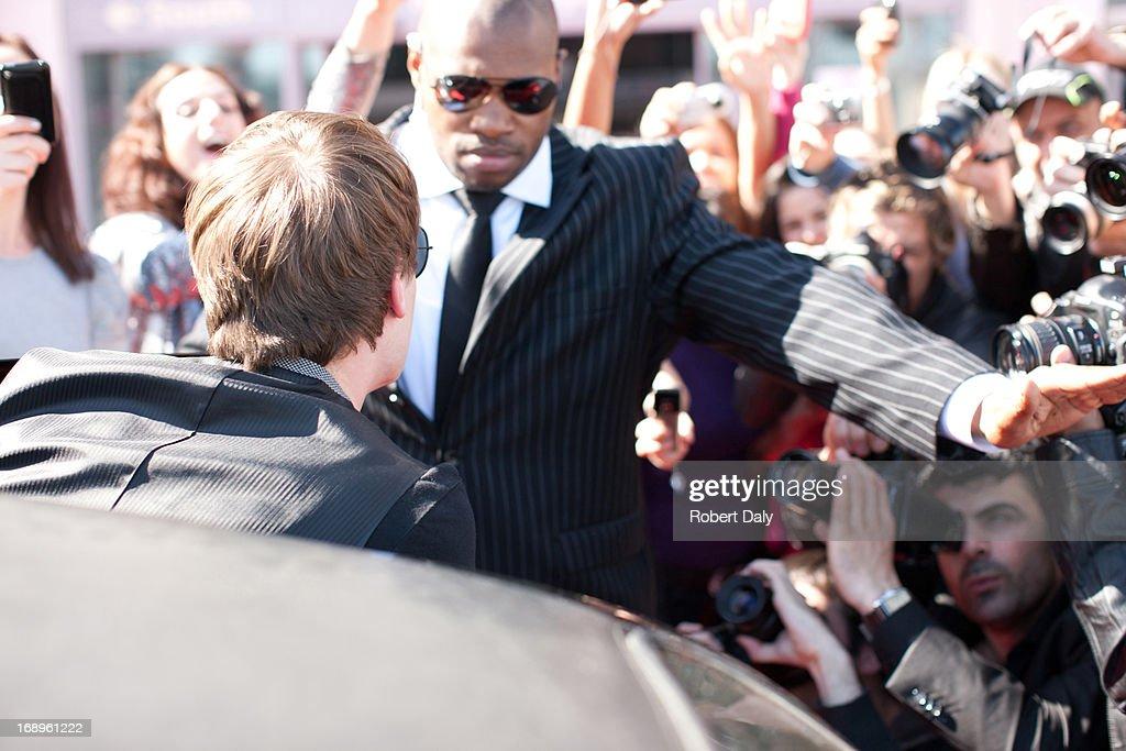 Celebrity emerging from limo toward paparazzi : Stock Photo