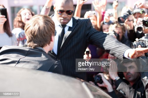 Celebrity emerging from limo toward paparazzi