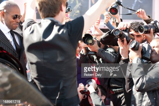 Celebrity emerging from limo towards paparazzi : Stock Photo