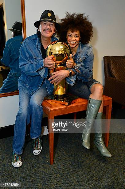 Celebrity guitarist Carlos Santana with wife Cindy Blackman Santana pose with the trophy before the game between the Cleveland Cavaliers and Golden...